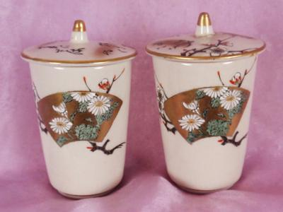 two matching cups with lids, one lid is repaired