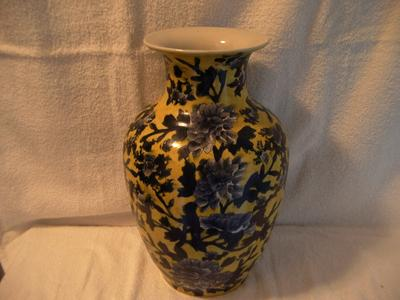 Yellow vase with blue flowers